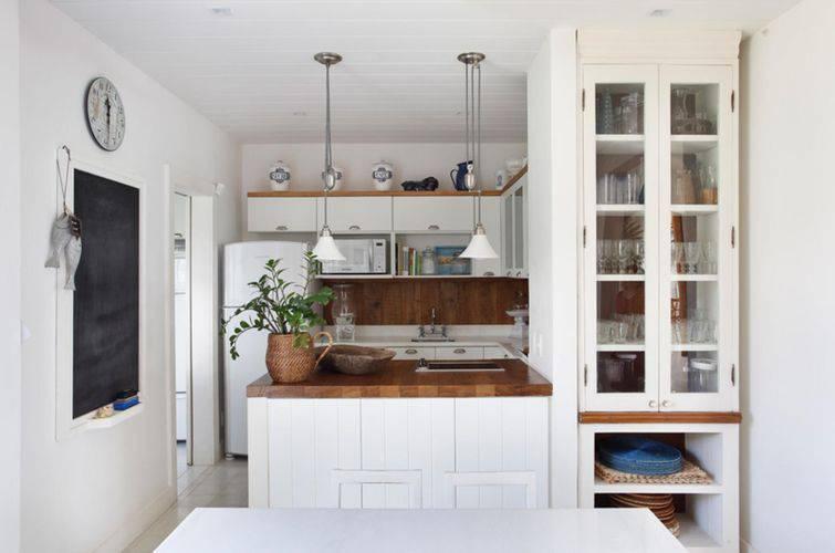 Decoração  com armários brancos e bancada de madeira.