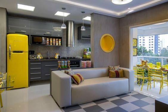 cozinha americana integrada a sala de estar amarela e cinza