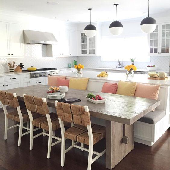 mesa de jantar com sofá e  cozinha americana.