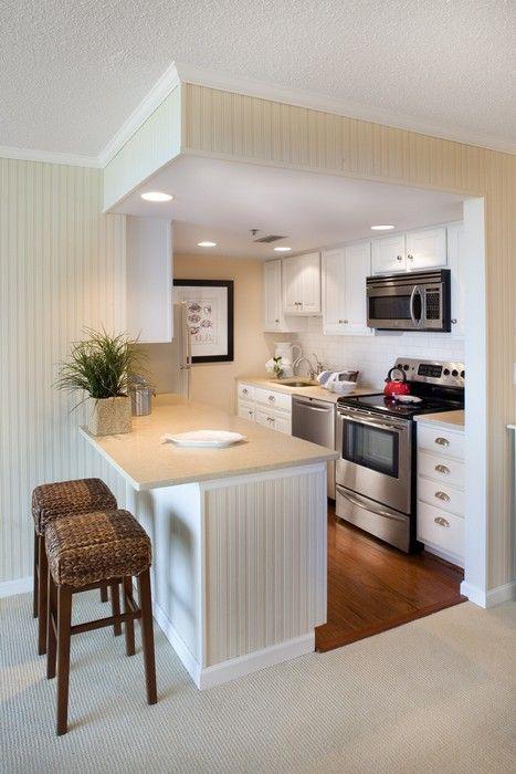 cozinha americana branca pequena com armários.