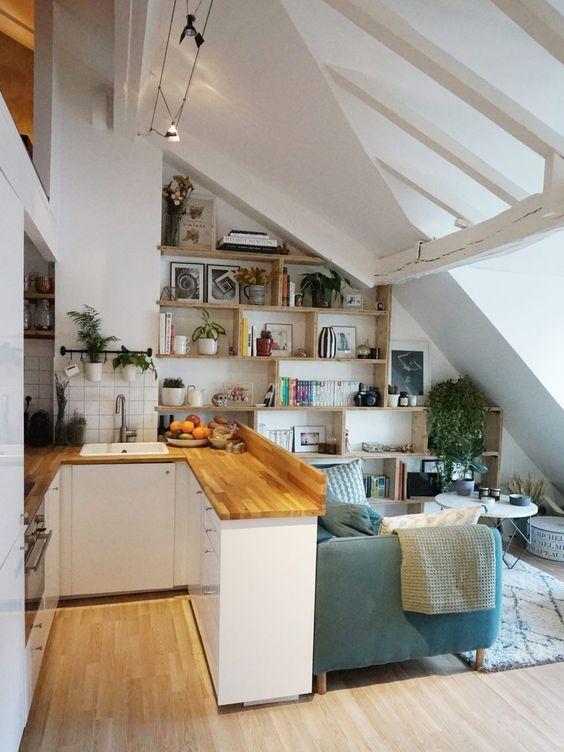 cozinha com sala de estar e teto inclinado.