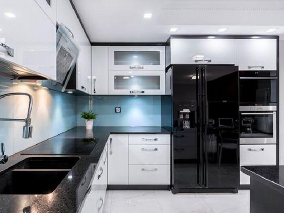 cozinha com bancada preta e geladeira side by side preta