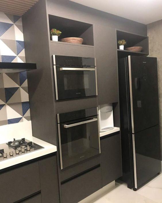 cozinha com geladeira preta e armários cinza
