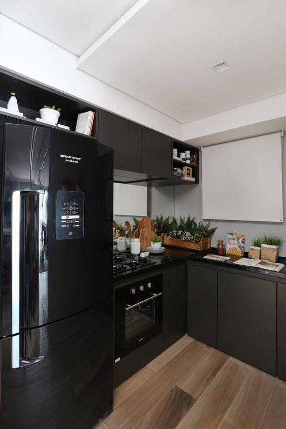 geladeira preta com armário cinza e bancada preta