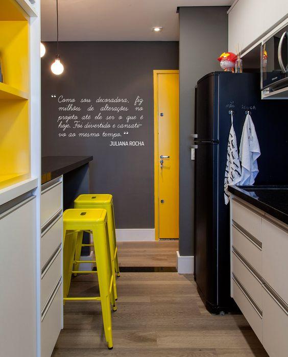 cozinha amarela e preta com geladeira preta