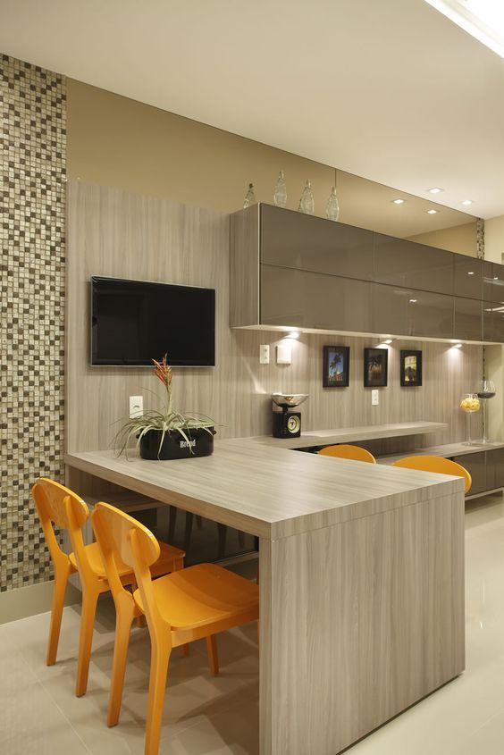 cozinha americana com tv e mesa para refeições.