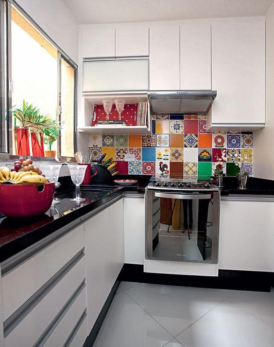 cozinha em l com azulejos coloridos e bancadas de granito preto