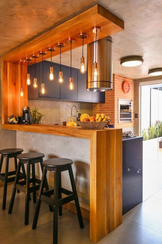 cozinha em L com bancada de madeira e pendentes industriais