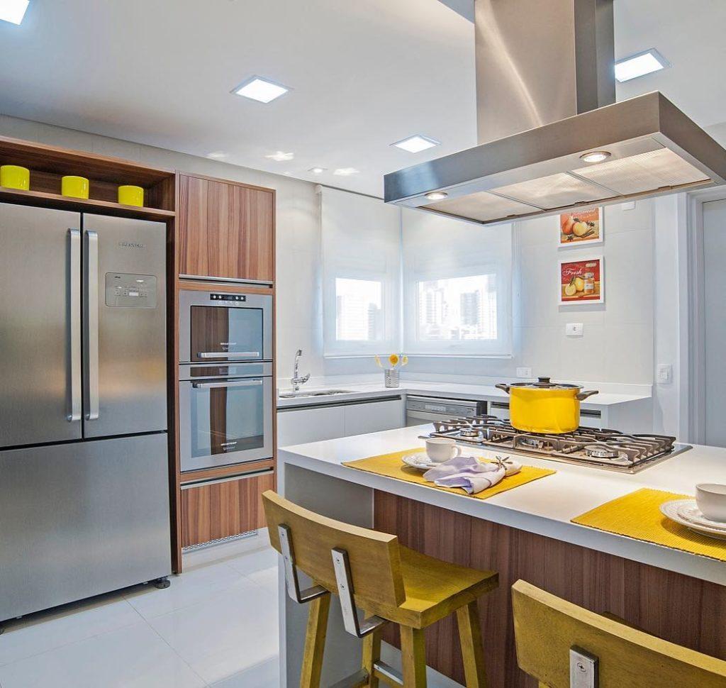 cozinha em l com ilha centra branca e coifa de inox