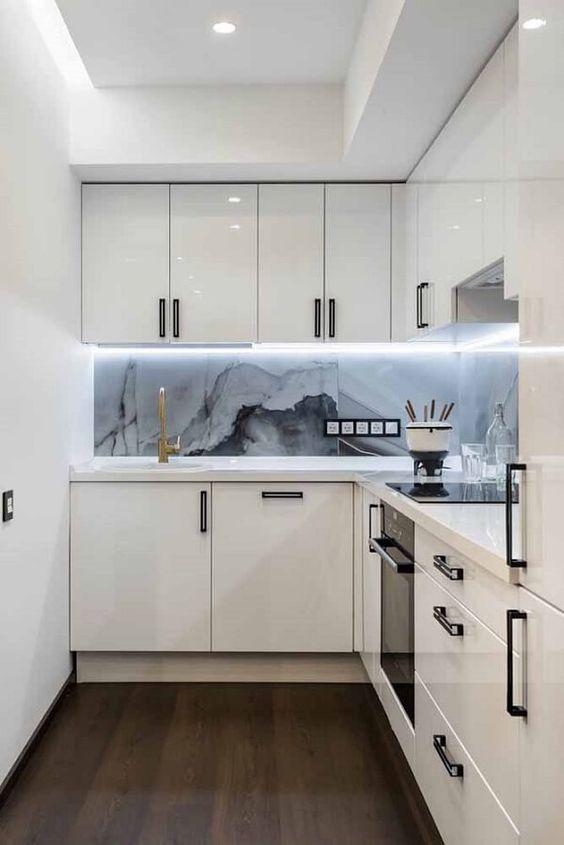 cozinha em L com frontão de mármore.