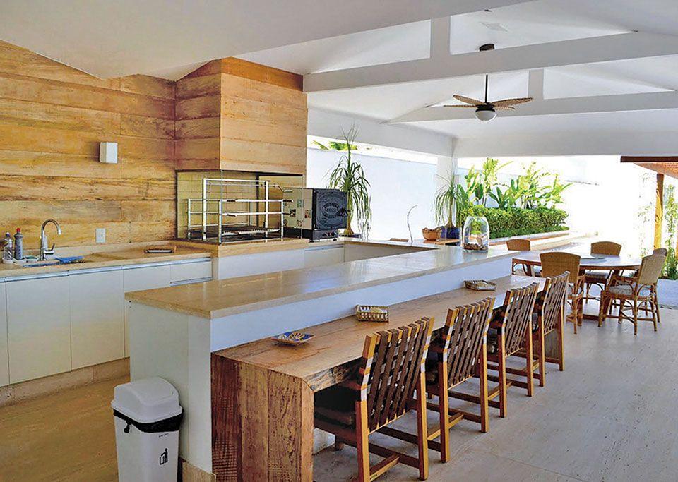 Grande cozinha gourmet externa com balcão e mesa redonda de madeira.