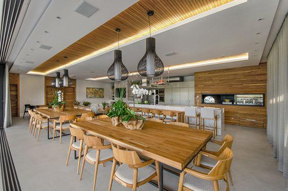 Grande cozinha com duas mesas de madeira decoradas com vasos de flores e plantas.