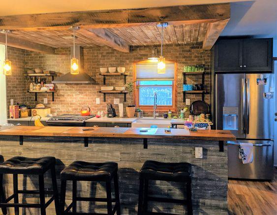 Cozinha gourmet com geladeira de duas portas, fogão e coifa.