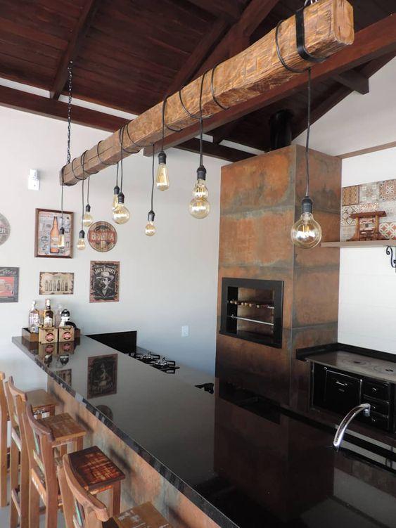 Cozinha gourmet externa com churrasqueira e fogão a lenha.