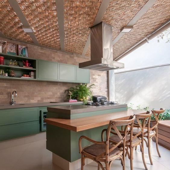 Cozinha de área externa com ilha, balcão e banquetas.