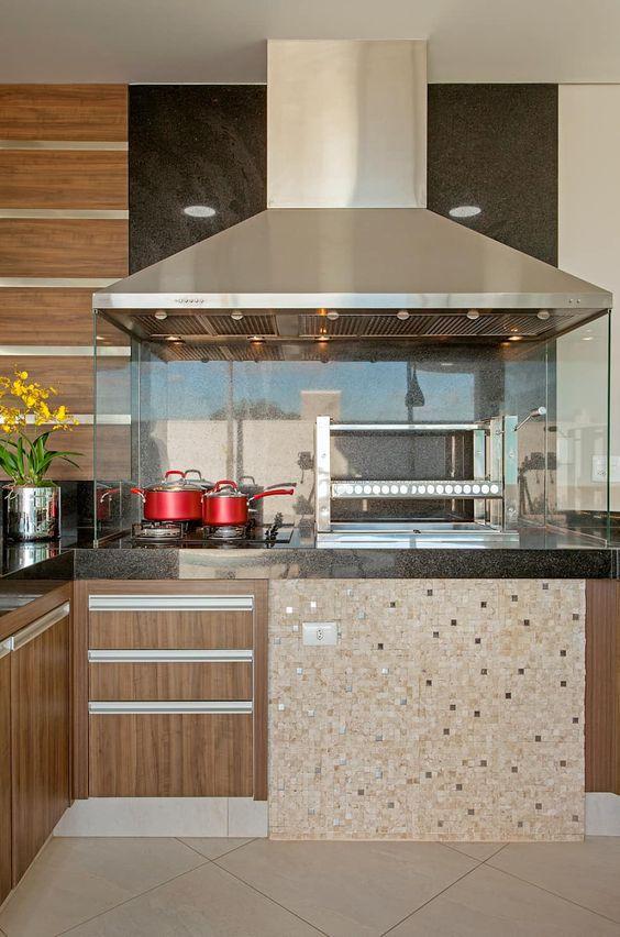 Cozinha com paredes de vidro separado o fogão e a churrasqueira do restante do balcão.