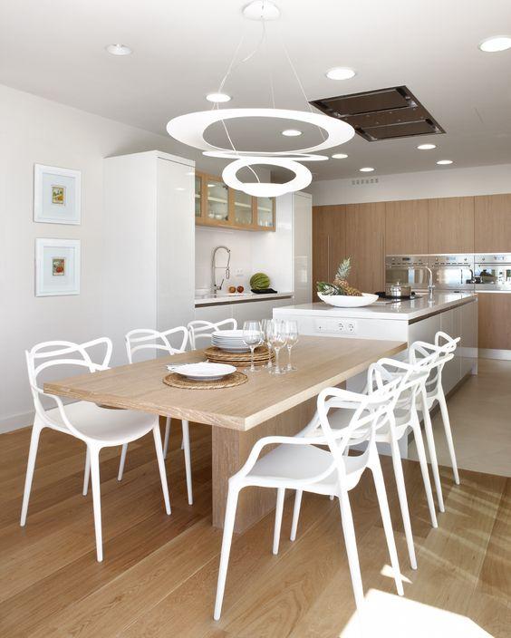 Sala de jantar com cadeiras brancas futuristas.