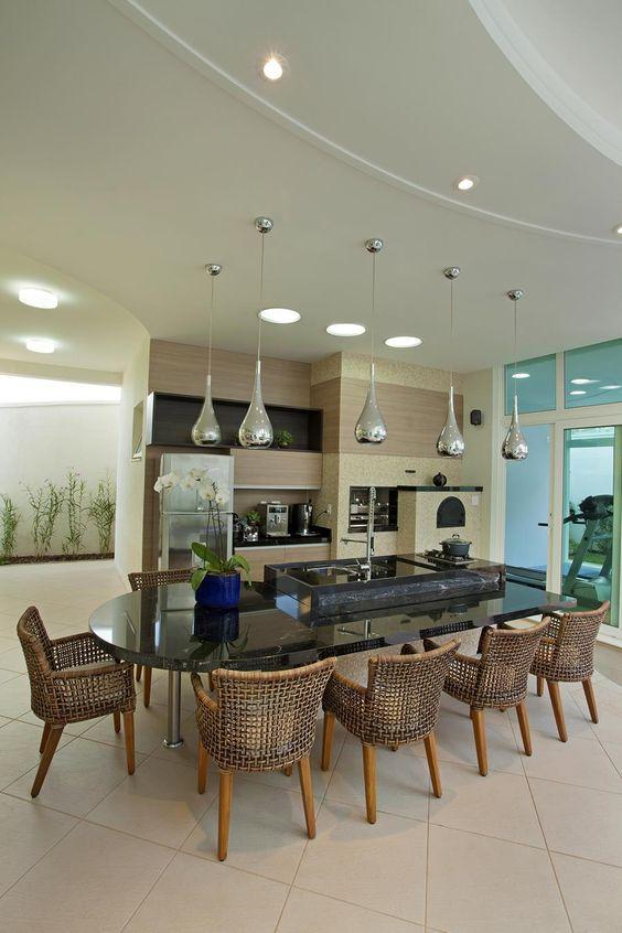 Cozinha gourmet integrada com sala de jantar com mesa em volta da ilha.