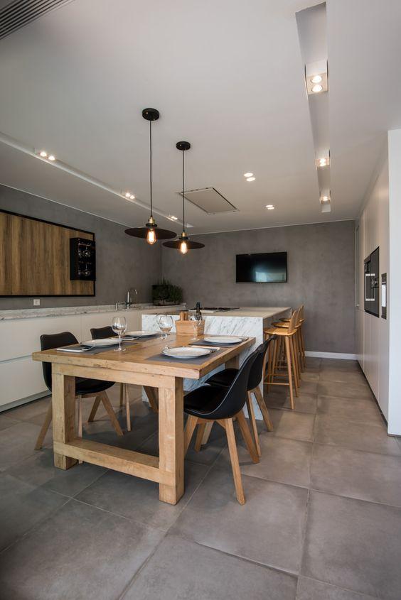 Cozinha e sala de jantar com banquetas e cadeiras de cores diferentes.