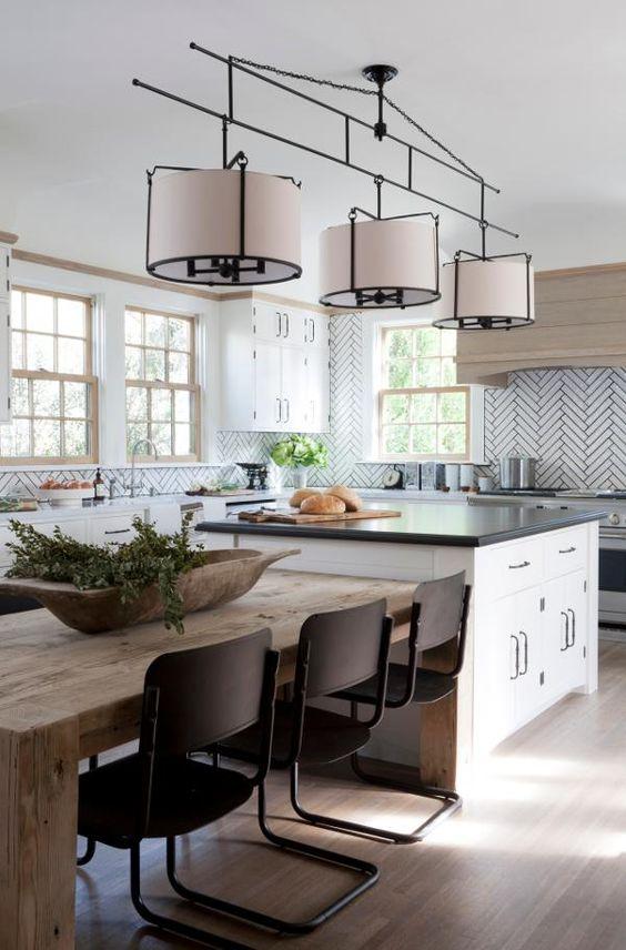 Cozinha gourmet com ilha, mesa de madeira e três lustres futuristas.