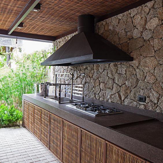 Cozinha externa com cooktop e churrasqueira embutidos na bancada.