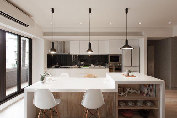 Cozinha e sala de jantar unidas por uma ilha com mesa.