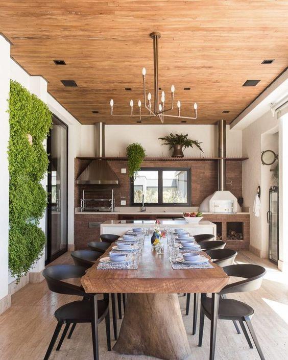 Sala de jantar com mesa rústica integrada com a cozinha externa.