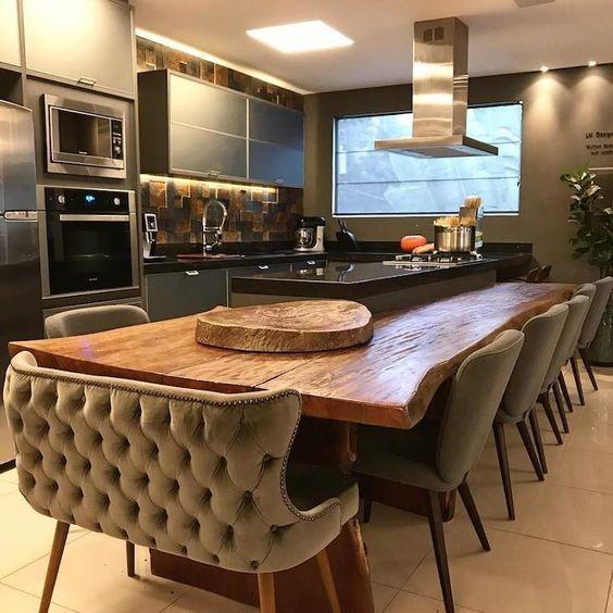 Mesa de madeira planejada em volta de balcão da cozinha.
