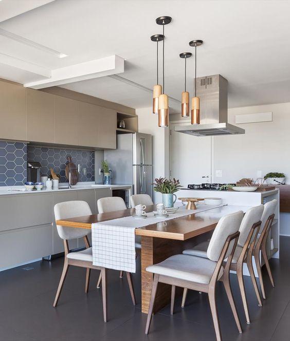 Cozinha integrada a sala de jantar decorada com iluminação suspensa.