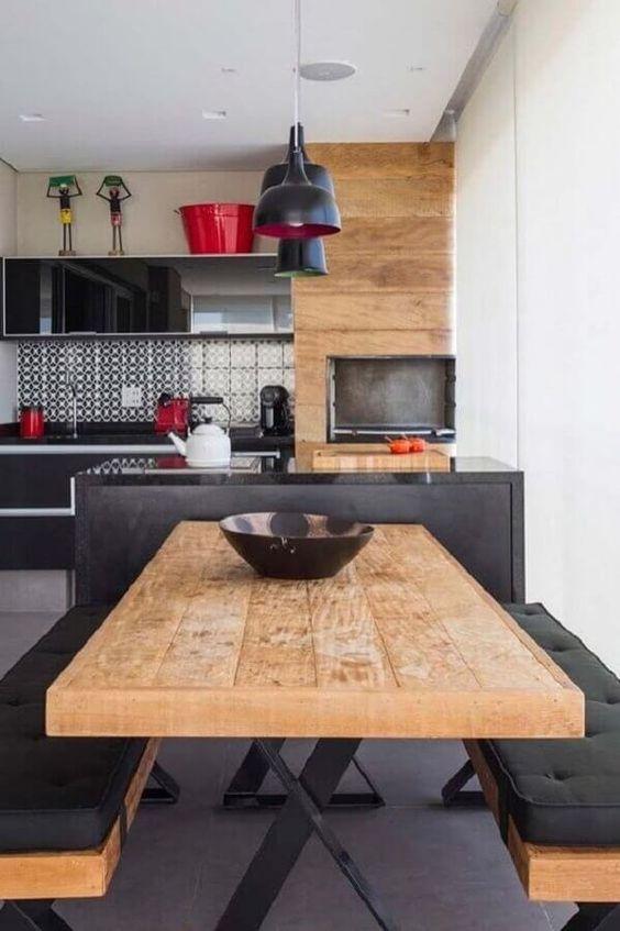 Cozinha integrada com mesa de jantar e bancos de madeira com estofados pretos.