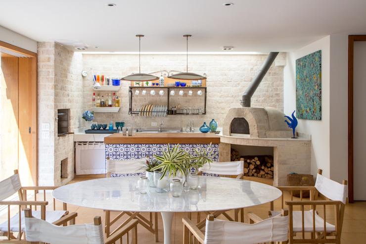 Cozinha externa com forno a lenha e porta de vidro.