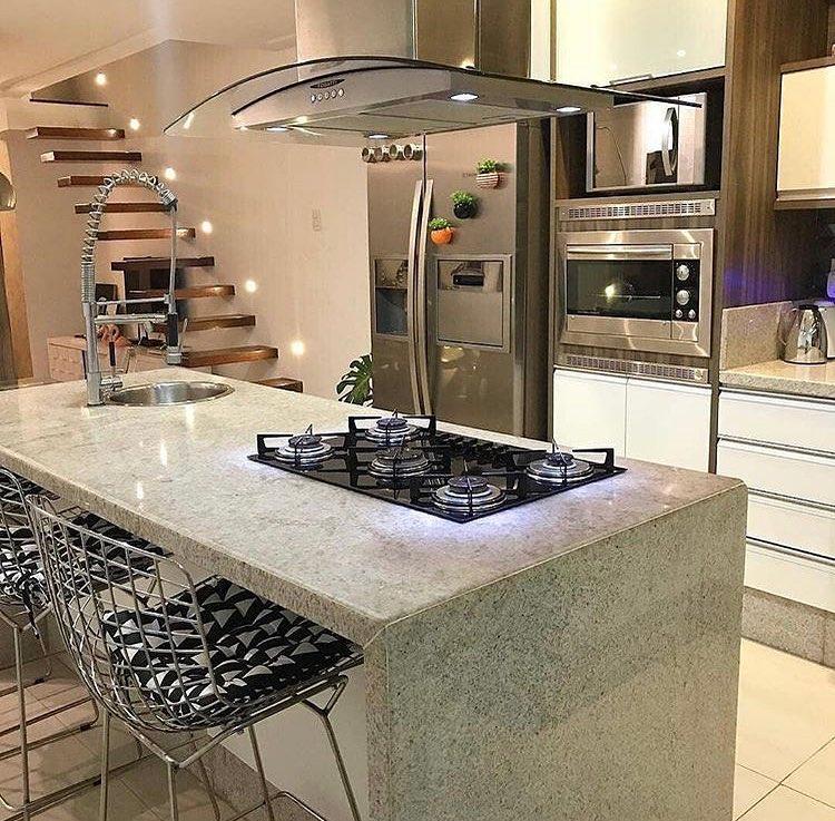 Revestimento de ilha da cozinha com pedra de mármore, cooktop e pia redonda.