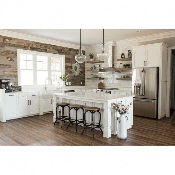 Cozinha com balcão central branco de apoio.
