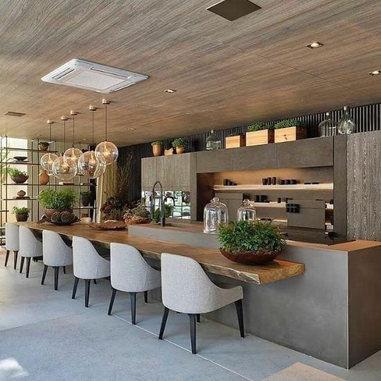Cozinha gourmet externa com balcão de madeira e cadeiras cinzas.