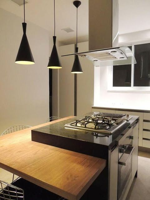 Decoração de cozinha com três luminárias suspensas.