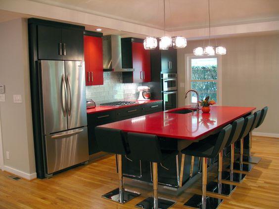 Cozinha com apoio central vermelho e sete banquetas.