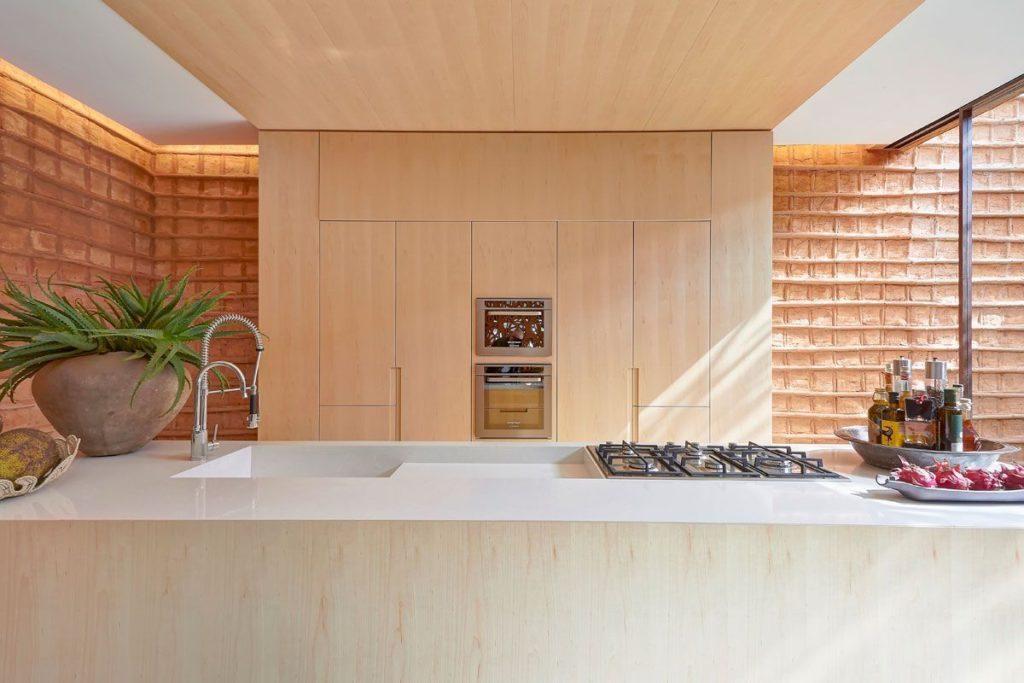 Cozinha minimalista com fornos embutidos centralizados na parede.