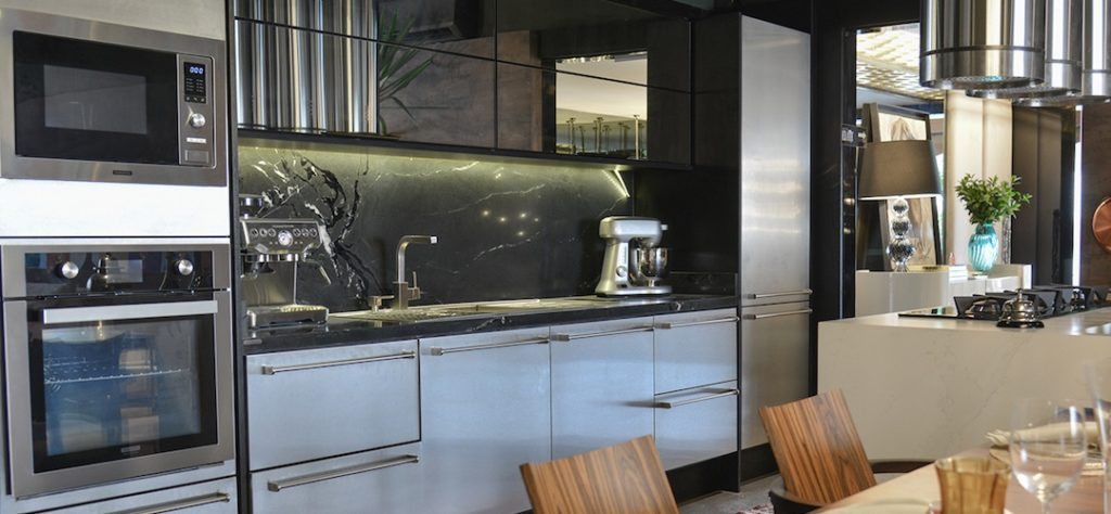 Cozinha com revestimento escuro e eletrodomésticos embutidos no armário.