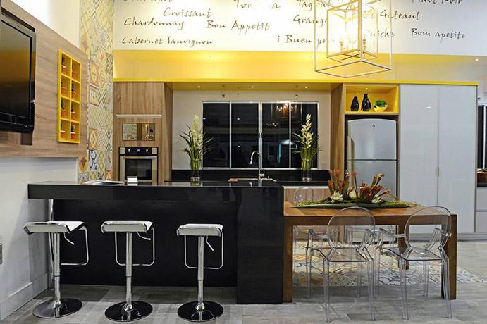 Cozinha decorada com banquetas e cadeiras diferentes.