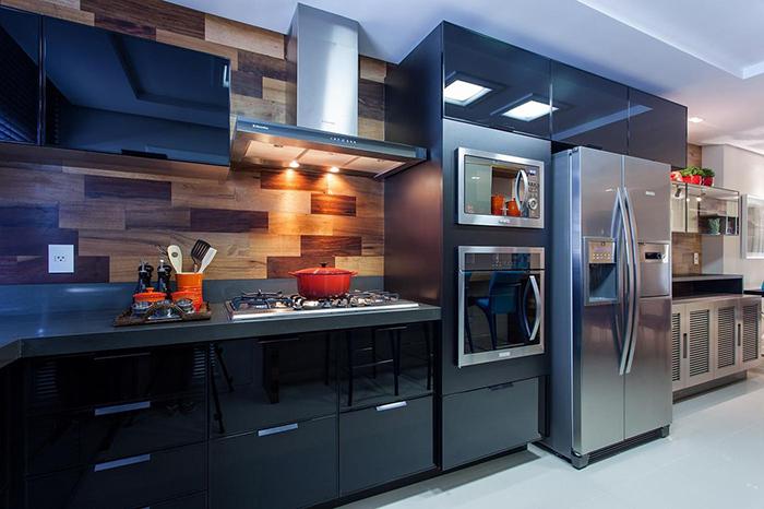 Decoração de cozinha com armários escuros e microondas e forno embutidos.