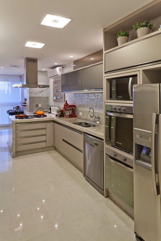 Cozinha equipada com cooktop, lava-louça, fornos, microondas e geladeira.