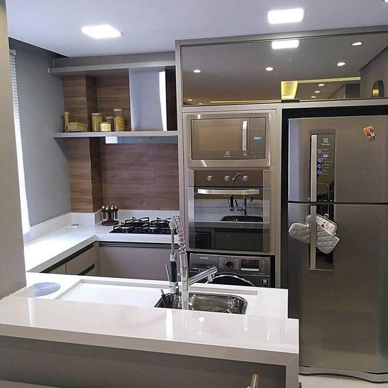 Pequena cozinha com eletrodomésticos embutidos na vertical e armários cinza.