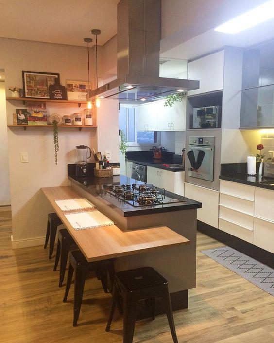 Decoração de cozinha com forno embutido no armário e cooktop no balcão.