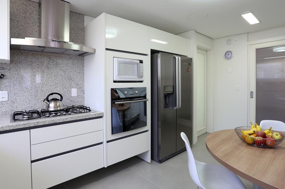 Cozinha planejada com armários brancos.