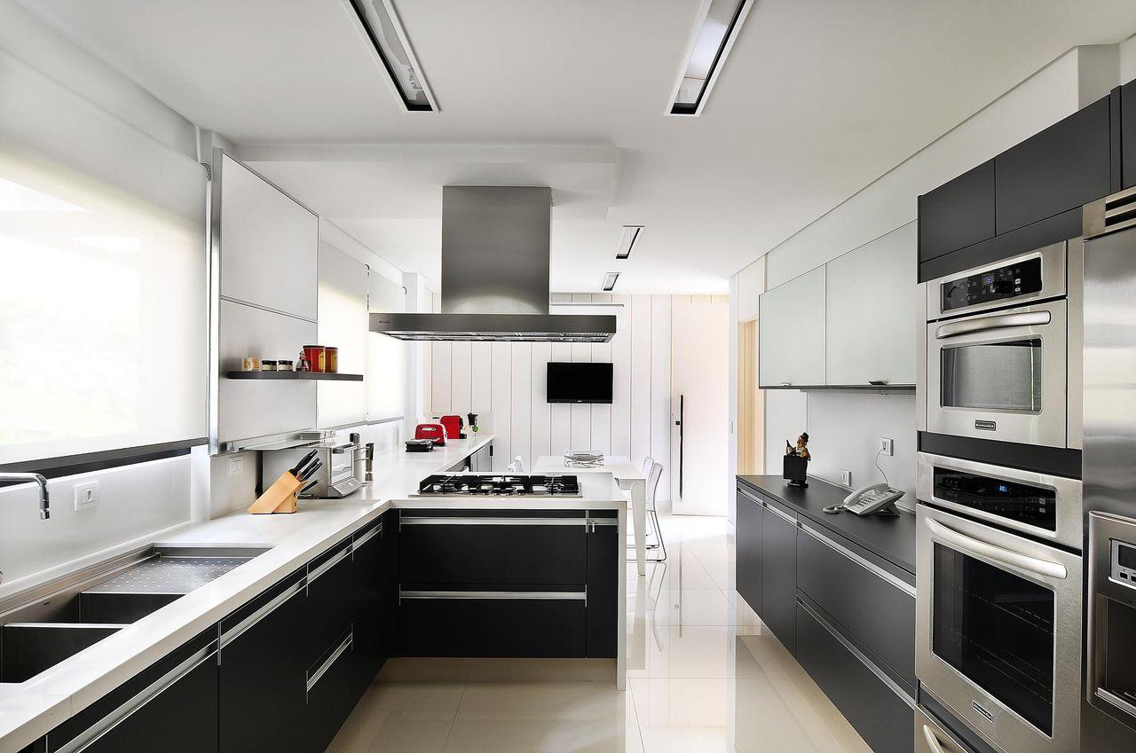 Cozinha planejada com armário preto e bancada de mármore.