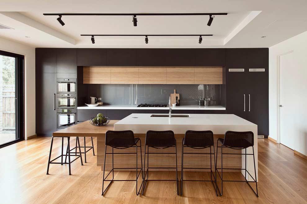 Decoração luxuosa e moderna com armários de madeira e acabamento preto.