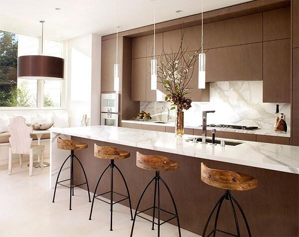Cozinha planejada com armários marrom e ilha de mármore.