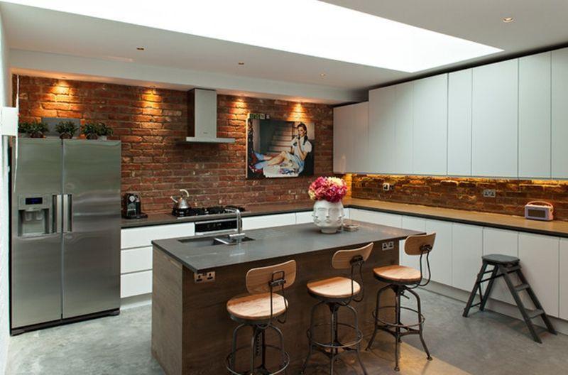 Cozinha planejada com spots de led e parede de tijolinho aparente.