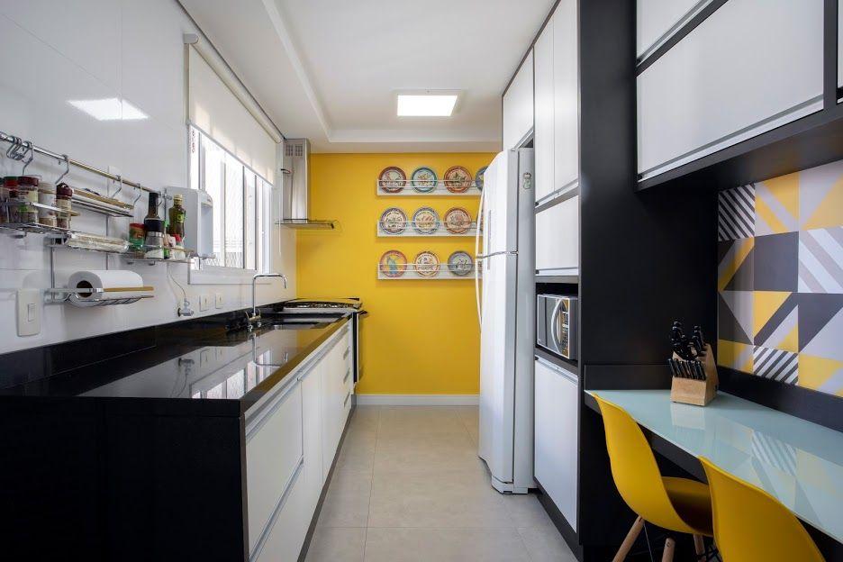 Cozinha planejada com decoração amarela e mesa de vidro.
