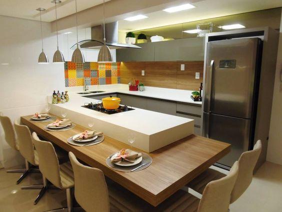 Cozinha americana com mesa de madeira.